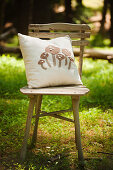 Mushroom-patterned cushion on chair in sunny woodland clearing