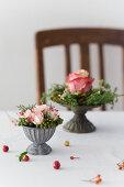 Kleine Blumengestecke in grauen Metallschälchen auf dem Tisch
