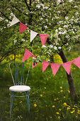 Delicate chair below bunting hung from flowering cherry tree