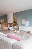 Hanging chair and Christmas tree in front of fire in living room with blue wall