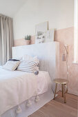 Bed with marbled headboard in bedroom in pastel shades