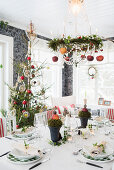 Festlich gedeckter Esstisch unter hängendem Weihnachtskranz