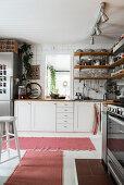 Regalbretter über Unterschränken in heller Küche mit Teppichen