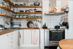Shelves on walls above base units and white wall tiles in kitchen