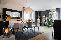 Festlich gedeckter Tisch in offenem Wohnraum mit Weihnachtsbaum