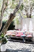 Weihnachtlich gedeckter Tisch mit Holzbank auf sonniger Terrasse