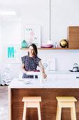Küchentheke mit Marmorplatte, Pendelleuchte und Barhocker, Frau hinter Theke