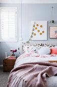 Doppelbett, Pendelleuchte und Nachtkästchen in weihnachtlich dekoriertem Schlafzimmer