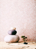Three large stones and bonsai against a wallpapered wall