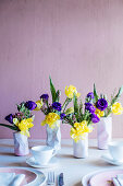 Spring flowers in three vases shaped like crushed tin cans