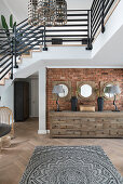 Chest of drawers against brick wall below staircase in open-plan interior