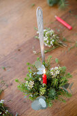 Festive flower arrangement with candle in ladle