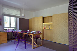 Dining table and purple chairs in front of kitchenette with sliding doors