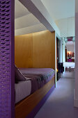 Bed hidden by partition wall, ensuite bathroom and purple accents