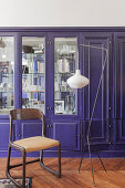 Vintage chair and standard lamp in front of purple fitted cupboards