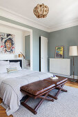 Leather stools at foot of bed in white-and-grey bedroom
