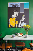 Pop art picture on green wall above dining table