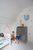 Child next to grey cabinet and whit bed in attic nursery