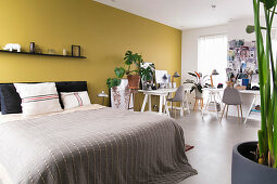 Two desks arranged in an L in bedroom with yellow wall