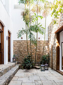 Stone walls and palms in courtyard garden between two buildings