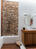Open, floor-level shower with stone wall