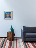 Sculpture of peacock next to grey sofa on striped rug