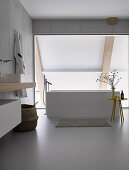 Free-standing bathtub in modern bathroom with glass wall