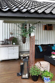 Sofa and rustic accessories on roofed terrace