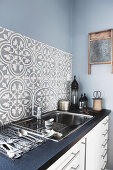 Splashback of classic patterned tiles above sink