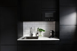 Modern, black fitted kitchen with white worksurface in niche