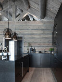Black kitchen in log cabin with exposed roof structure