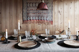 Dining table set with linen cloth, wooden plates and crystal glasses