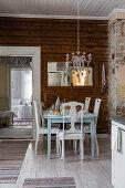 Gedeckter Tisch mit Stühlen, darüber Kronleuchter mit altem Silberbesteck