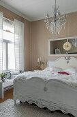 Weißes Holzbett und Kronleuchter in nostalgischem Schlafzimmer mit Tapete