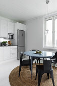 Round table and chairs on round rug next to white kitchen counter