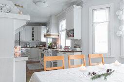 Esstisch mit Weihnachtsdekoration und weiße Küche in offenem Wohnraum