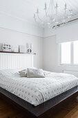Doppelbett mit Kopfteil aus Holz und weißer Kronleuchter im Schlafzimmer
