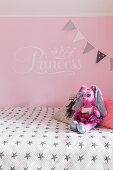 Plüschfigur auf Bett vor rosa Wand im Mädchenzimmer