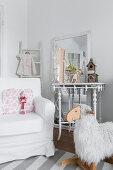 Weißer Hussensessel, Konsole vor Wandspiegel und Schaukelschaf
