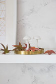 Two mushroom ornaments and autumn leaves on golden tray