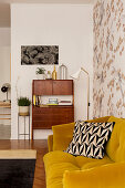 Mustard-yellow sofa against patterned wallpaper and 50s cabinet in living room