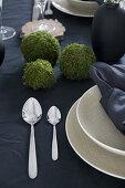 Table set with dark linens, beige crockery and handmade moss balls