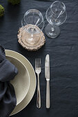 Table set with dark linens, beige crockery and wooden coasters