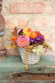 Arrangement of brightly coloured autumn flowers in basket
