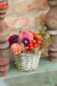 Colourful arrangement of autumn flowers and tomatoes in basket