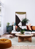 Wooden coffee table, sofa with brunette woman, house plants and picture on sideboard in living room