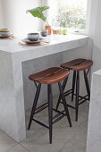 Two stools below crockery in earthy shades on marble table