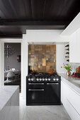 Mosaic of bronze-coloured tiles above modern gas cooker