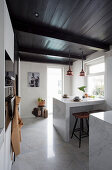 Dining area in modern country-house kitchen with marble elements