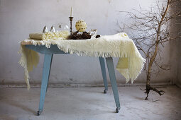 Woollen blankets and wintry accessories on blue wooden table